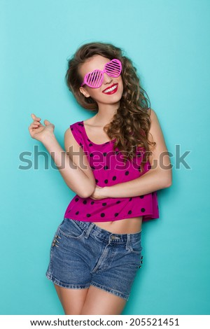 Smiling sexy girl in pink sunglasses. Smiling beautiful young woman pointing. Three quarter length studio shot on teal background. - stock photo