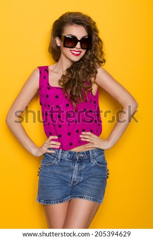 Smiling sexy girl in sunglasses. Beautiful young woman in sunglasses posing with hand on hips. Three quarter length studio shot on yellow background. - stock photo