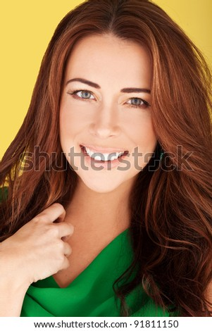 Smiling sexy redhead women wearing emerald green dress, in beauty and glamour portrait on yellow. - stock photo