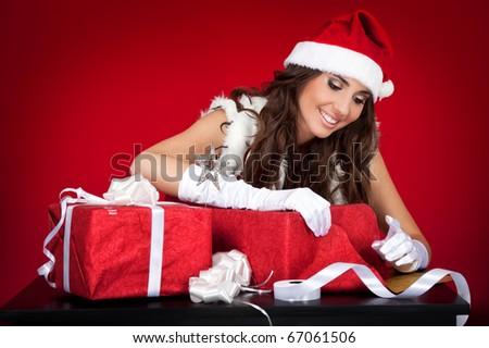 smiling sexy santas helper wrapping Christmas presents - stock photo