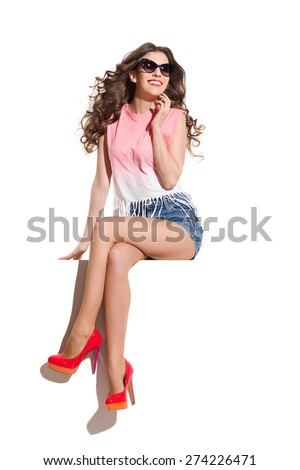 Smiling sexy woman in sunglasses, pink top, jeans shorts and red high heels sitting at the white banner and looking away. Full length studio shot isolated on white. - stock photo