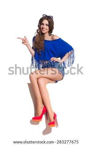 Smiling sexy young woman in blue top, jeans shorts and red high heels sitting on a top of white banner, pointing and looking away. Full length studio shot isolated on white. - stock photo