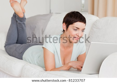 Smiling short-haired woman using a laptop in her living room