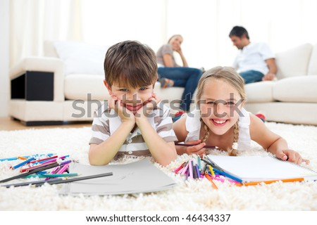 Smiling siblings drawing lying on the floor in the living room - stock photo