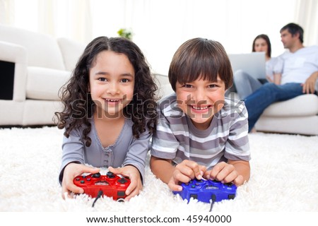 Smiling siblings playing video games lying on the floor with their parents in the background - stock photo