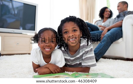 Smiling siblings reading lying on the floor in the living room - stock photo