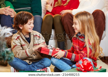 Smiling sister giving her brother a gift for christmas - stock photo