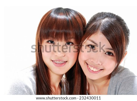 smiling sisters portrait on white - stock photo