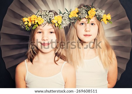 Smiling sisters, portrait with flowers - stock photo