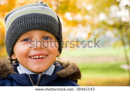 Smiling small boy and yellow autumn scenery - stock photo