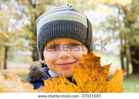 Smiling small boy and yellow leaves in autumn - stock photo