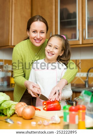 Smiling small girl helping mother to make soup at kitchen