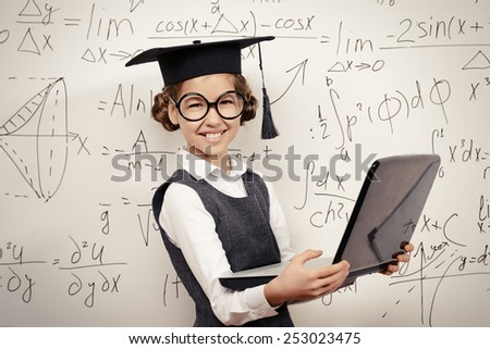 Smiling smart schoolgirl in big glasses and academic hat performs the task at the blackboard with a laptop. Education. - stock photo