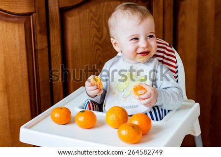 Smiling smudgy baby with mandarines - stock photo