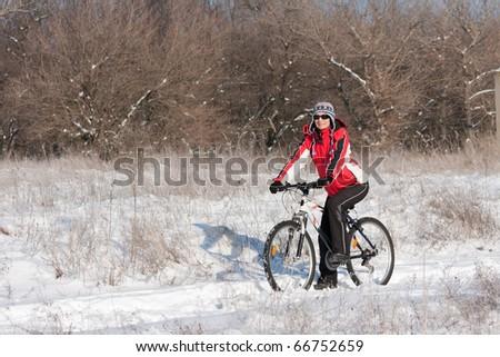 Smiling snow biker on the sunset - stock photo