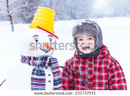 Smiling snowman with bucket and striped scarf and little cheerful  boy (kid) are standing on winter background. Happy child is enjoying view  of winter day. New year, christmas, winter concept.  - stock photo