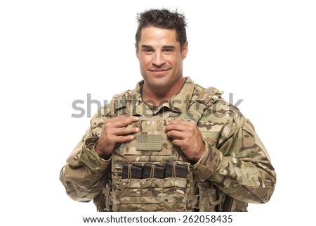 Smiling soldier in protective wear / tactical vest posing against white background - stock photo