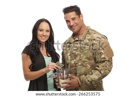 Smiling soldier with his wife collecting money in jar against white background - stock photo