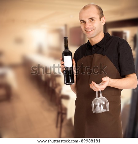 Smiling sommelier presenting a wine bottle with a blank label and a pair of glasses in a restaurant - stock photo