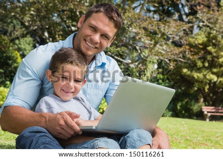 Smiling son and dad with a laptop on their knees in the park - stock photo