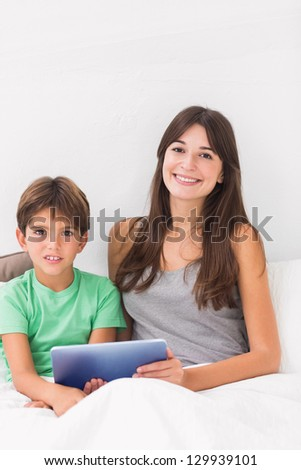Smiling son and mother using digital tablet in bed