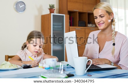 Smiling spanish businesswoman browsing internet at home, daughter drawing  in pencil