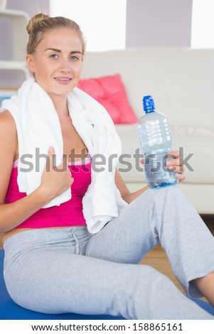 Smiling sporty blonde sitting on exercise mat holding water bottle in bright living room - stock photo