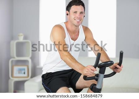 Smiling sporty man exercising on bike and listening to music in bright living room - stock photo