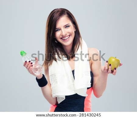 Smiling sporty woman holding apple and bottle with water over gray background. Looking at camera - stock photo
