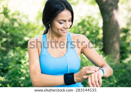 Smiling sporty woman in headphones using smart watch outdoors in park - stock photo