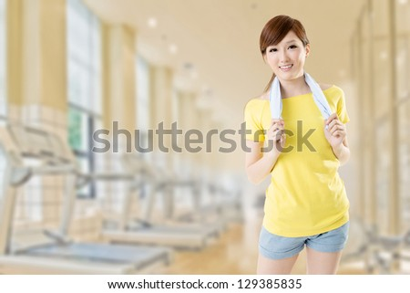 Smiling sporty woman take a rest after training, closeup portrait at gym. - stock photo