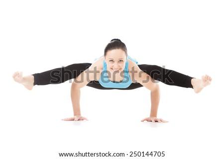 Smiling sporty yogi girl doing fitness exercises, handstand, yoga asana Tittibhasana, arm balance Firefly posture, Insect Pose, isolated on white background - stock photo