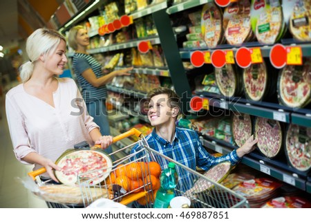 Smiling spouses buying Italian pizza in cooled food section