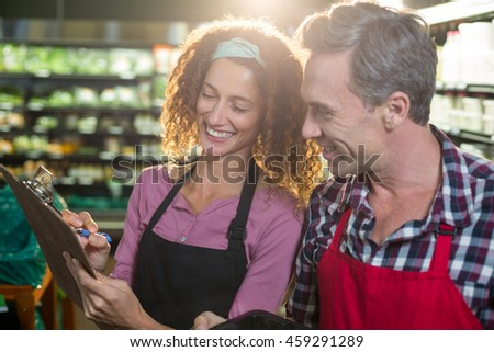 Smiling staffs writing on clipboard in organic section of supermarket - stock photo