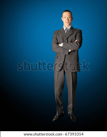 smiling standing businessman in suit isolated on blue - stock photo
