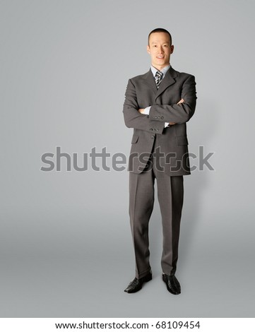 smiling standing businessman in suit isolated on gray - stock photo