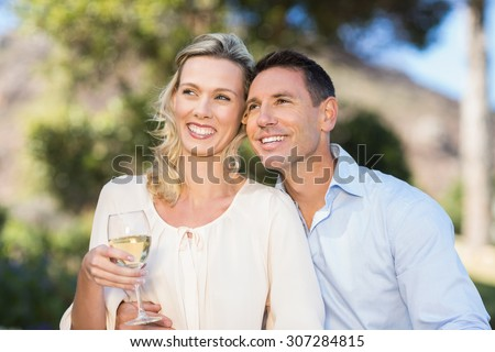 Smiling standing couple enjoying the view and holding wineglass in parkland