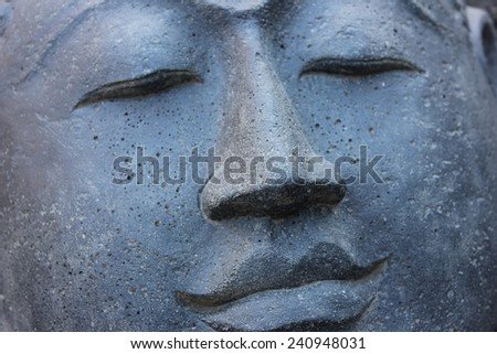 Smiling Stone Buddha Statue face with closed eyes from Indonesia looking to the right - stock photo