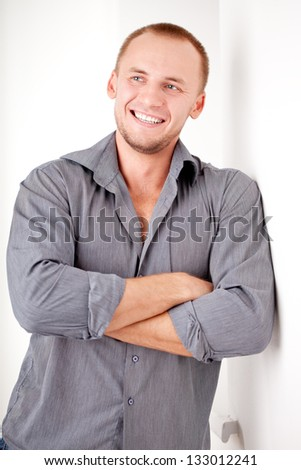 smiling strong casually dressed man near white wall