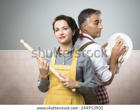 Smiling strong woman with rolling pin watching her husband cleaning dishes - stock photo