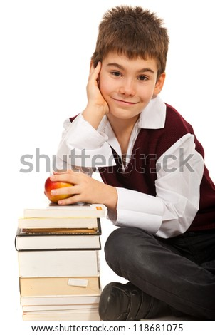 Smiling  student boy  holding apple and resting hand on books isolated on white background - stock photo