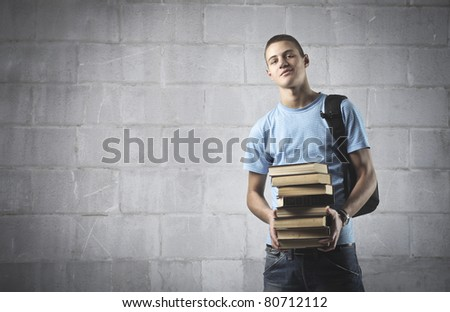 Smiling student carrying some books - stock photo