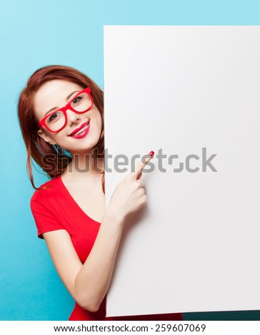 Smiling student girl in red dress and glasses with white board on blue background - stock photo