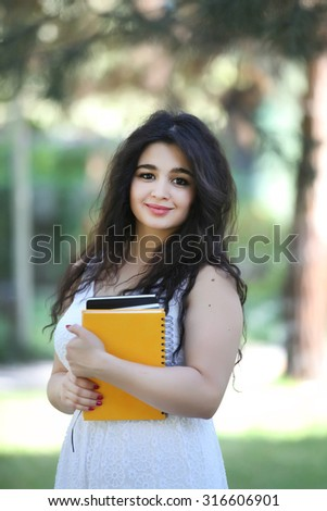 smiling Student girl outdoors with bag on backside and with notebook on hand, exercise book, drawing block, girl with white dress, smiling girl, Girl outdoors sitting and writing on notebook - stock photo