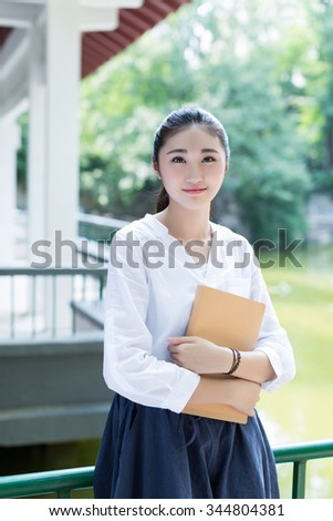 smiling student girl reads a books,  in the green park - stock photo
