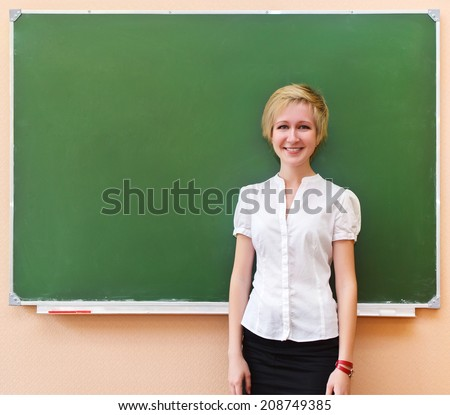 Smiling student girl standing near blackboard in the classroom - stock photo