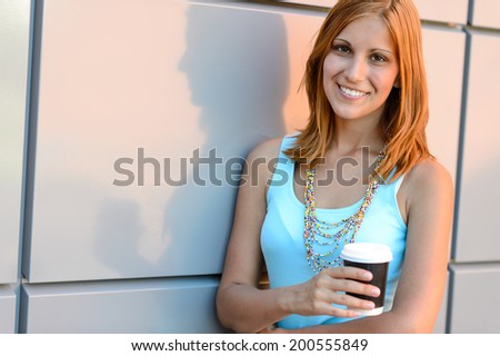 Smiling student girl with coffee cup summer standing by wall