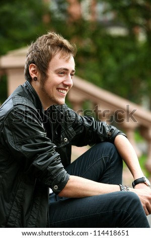 Smiling student guy on the street - stock photo