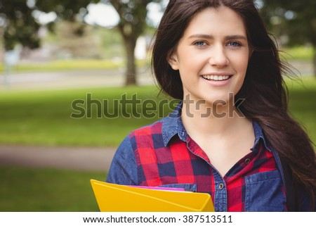 Smiling student holding binder at park - stock photo