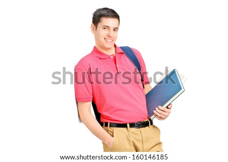 Smiling student holding books and leaning against wall isolated on white background